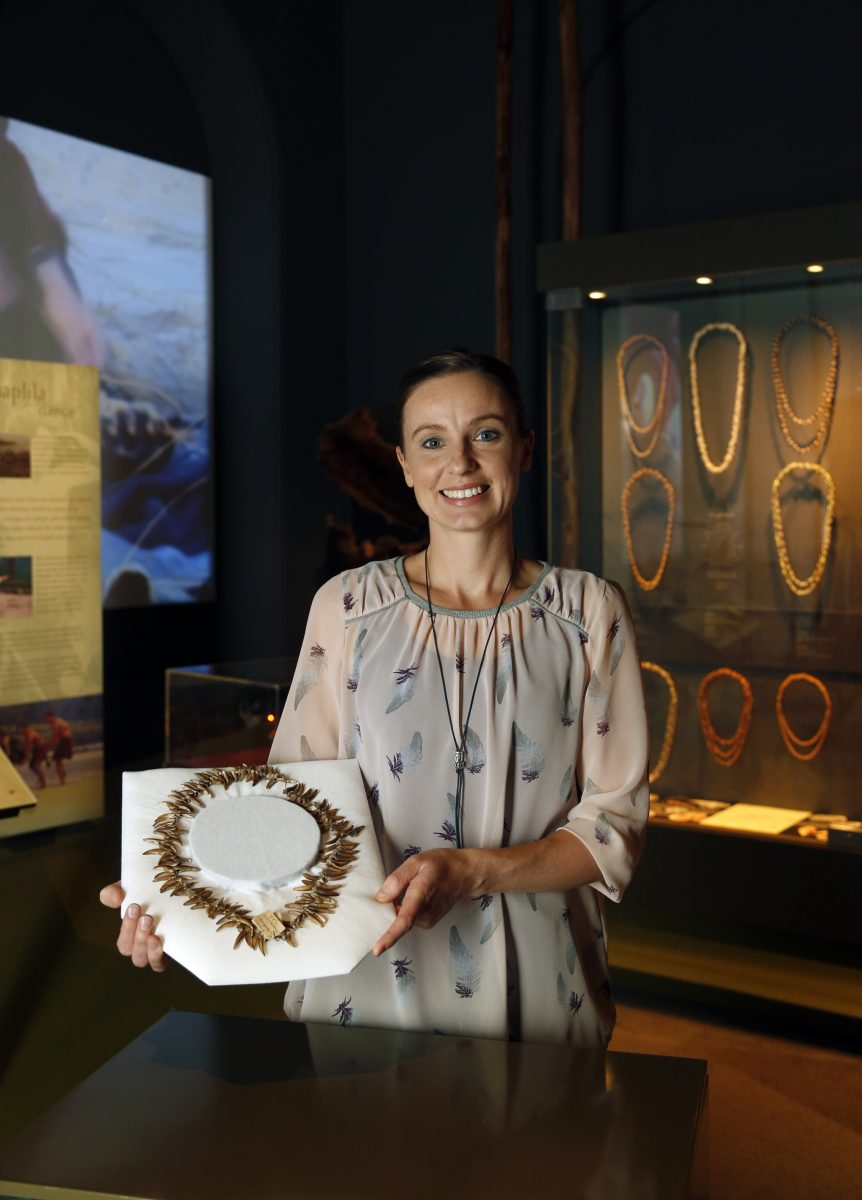 Photo of Zoe Rimmer at Tasmanian Museum and Art Gallery holding claw necklace