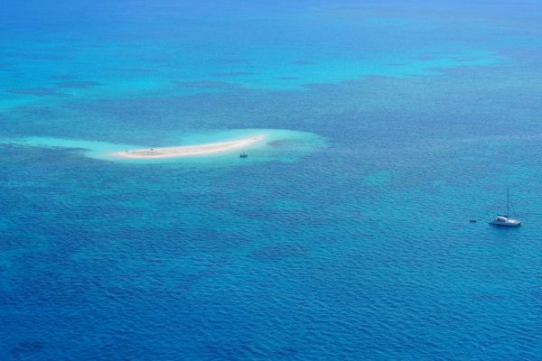 Different shades of blue sea with a small island of sand. Two boats on the water.