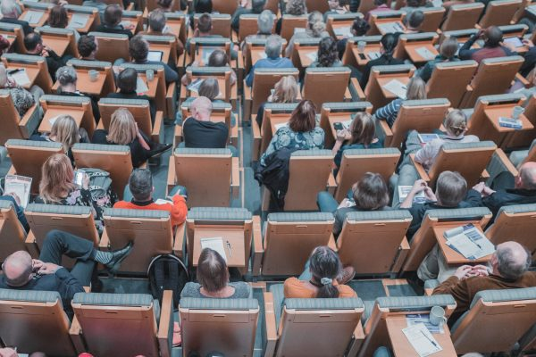 a birdseye view of a university lecture theatre with people sitting in chairs.